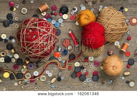 spools of thread yarn and colorful buttons on a wooden table