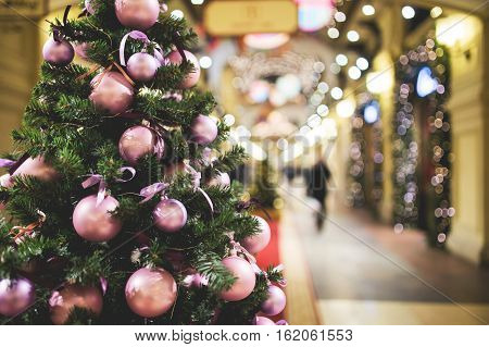 Christmas pine tree decorated with purple balls standing in lobby of store, toned photo