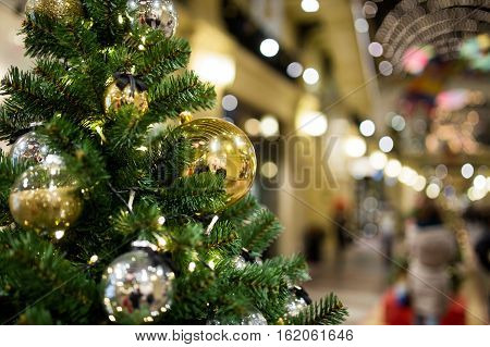 Festive fir with Christmas toys on background of shopping center