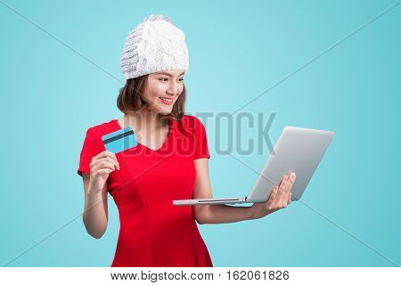 Winter Asian Woman Holding Laptop And Credit Card Against Blue Vignette