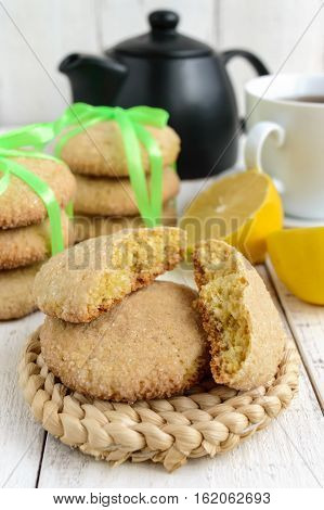 Shortbread lemon flavored cookies: a broken and connected green ribbon for a gift. Teapot and fresh lemon on a white wooden background. Close up