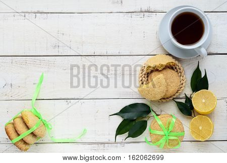 Shortbread lemon flavored cookies: a broken and connected green ribbon for a gift. Fresh lemon on a white wooden background. The top view
