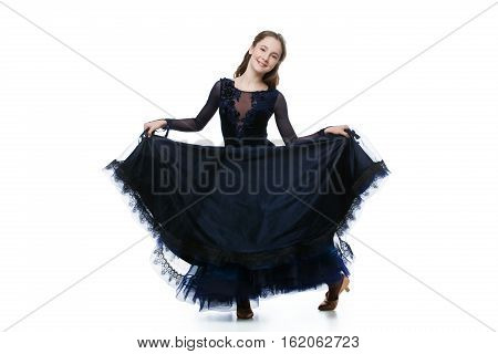 Beautiful teenager ballroom dancer with long blond hair in long dark blue dress making curtsy. Studio shot on grey background. Copy space.