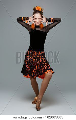 Beautiful teenage ballroom dancer girl in black and orange latina dress And accessories. Studio portrait on grey background. Copy space.