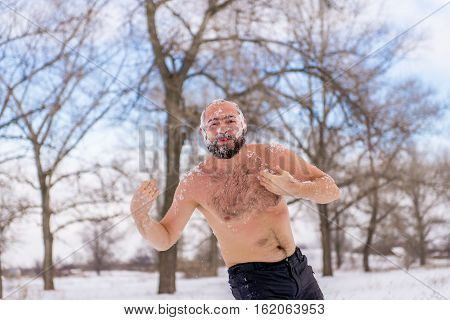 Young Man wiping snow in the winter to promote health. Hardening winter winter swimming.
