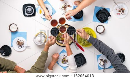 people clanging cups with tea together at the table with delicious desserts, top view