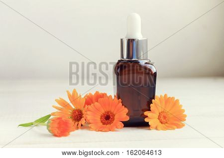 Dropper bottle of marigold extract, fresh flowers. Herbal oil skincare benefits. Toned.