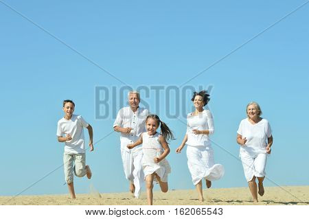Happy family runs together on sand beach
