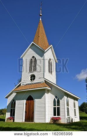 Beautiful rural white country church with a large belfry.