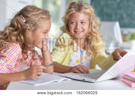 Portrait of two beautiful little girls at class