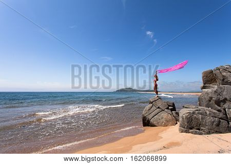Young slender woman on the sea rocky shore in a pink swimming suit and a pink fabric fluttering in the wind. Wide angle.