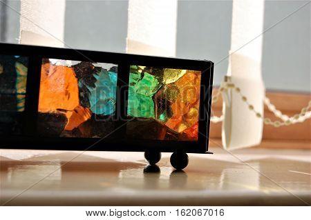 A colourful glass tea light candle holder on a windowsill