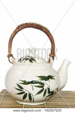 Asian teapot on bamboo mat plate - white background