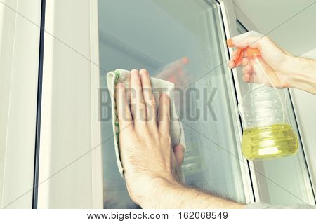 man washing windows with a special liquid