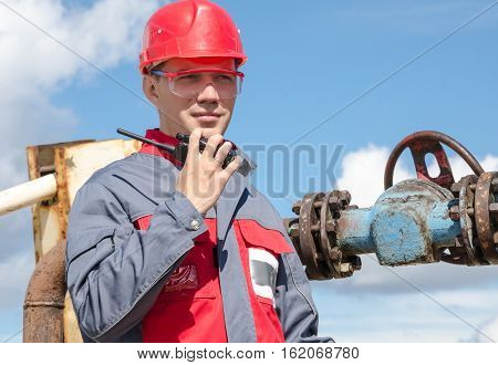Worker near wellhead valve holding radio and wearing red helmet in the oilfield. Oil and gas concept.