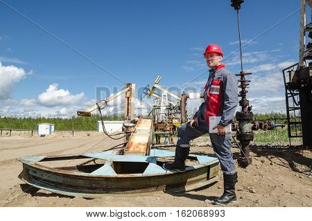 Worker near broken pump jack holding radio and tablet computer in the oilfield. Pump jacks and wellhead background. Oil and gas concept.