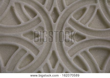 Carved bas-relief pattern on the surface of the marble stone