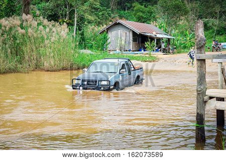 Ratchaburi,Thailand -Dec 4,2016: Four-wheel drive pickup truck were wading across the river in the forest.