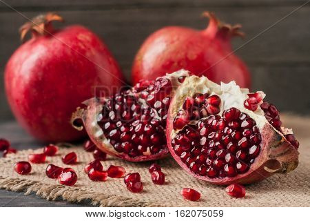 two pomegranate on the old wooden board with sackcloth.