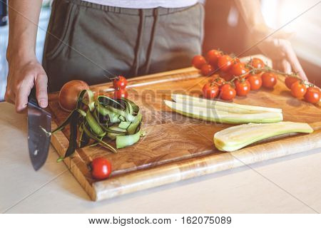 Female hand holding knife for cutting colorful fresh vegetables on a wooden board - Woman preparing healthy foods for her family - Warm vintage filter - Focus on the wood board