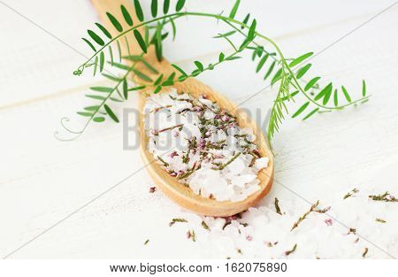 Wooden spoon of herbal salt for beauty care. Dried flowers and mineral mixture, bath blend. Soft light and focus.