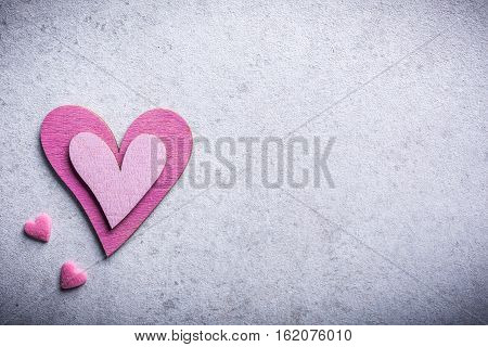 Valentines Day background with decorative pink wooden heart on concrete stone with copy space for text. Valentine's Day concept. View from above.