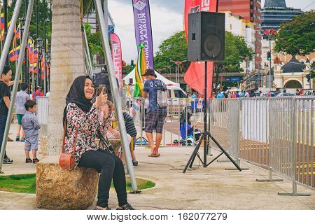 Kuala Lumpur, Malaysia - February 7, 2016: Young attractive smiling girl in hijab making selfie photo on smartphon against the background of The Sultan Abdul Samad Building