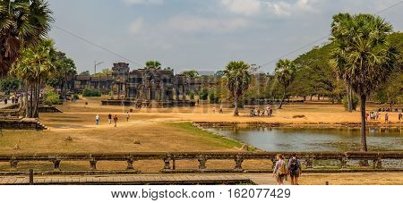 Siem Reap, Cambodia - February 1, 2016: Young tourists in front of the ruins and ancient pond of Angkor Wat temple, Siem Reap, Cambodia. The main road to Angkor Wat which runs tours