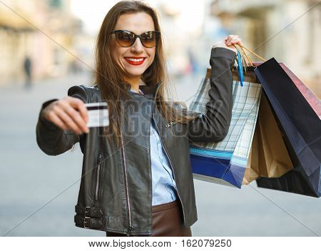 Sale shopping tourism and happy people concept - beautiful woman with shopping bags and credit card in the hands on a street