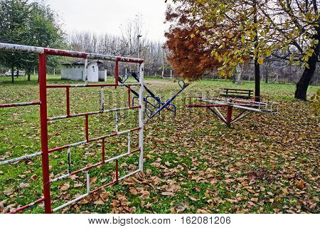 An empty playground on the bank of the river in autumn.