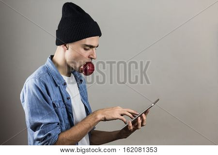 Man using tablet PC. Young male person in casual wear looks at a portable tablet computer while eating an apple