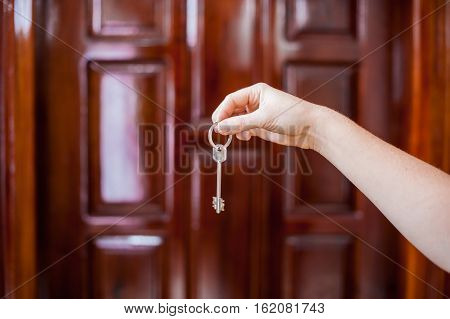 A Female Hand Holding A Key To The House On A Background Of A Wooden Door. Owning Real Estate Concep