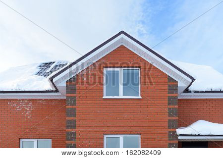 brick apartment house with a snow-covered roof