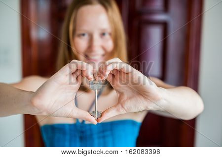 Women's Hands Hold House Key In The Form Of Heart On The Background Of A Wooden Door. Owning Real Es