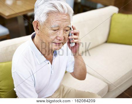 senior asian man sitting alone on sofa talking on mobile phone looking sad.