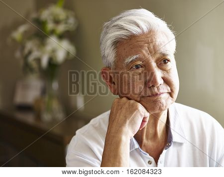 portrait of sad senior asian man hand on chin.