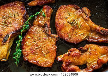 Roasted pork steaks cutlets with bones and thyme on black baking sheet top view.