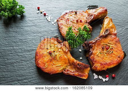 Roasted pork steaks cutlets with bones and fresh parsley on black stone background top view.