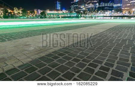 Green neon lights circulating underneath the stone seating reflecting on the stone pavement in Perth tourism hot spot Elizabeth Quay