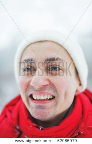 Young happy man in a red jacket and white cap laughing while walking in the winter eyebrows and eyelashes covered with snow close-up.