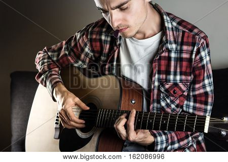 Young man playing chord on guitar. Male musician in casual wear plays acoustic instrument and holds pick in mouth