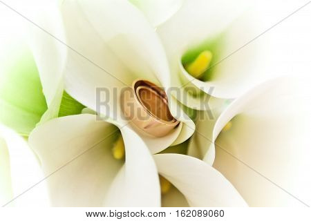 Wedding rings inside the bride's bouquet of callas