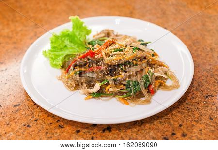 fried vermicelli with mushroom and white sesame on white plate korean food