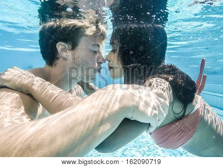happy couple underwater kissing and hugging eachother