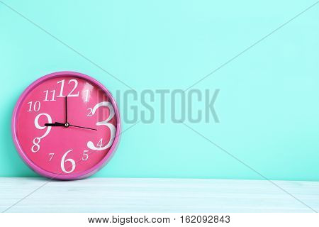 Pink Round Clock On A Green Background