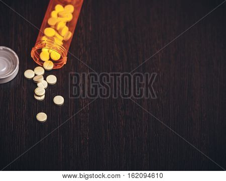 Top view of Vitamin pills and bottle on dark background. free copyspace for text