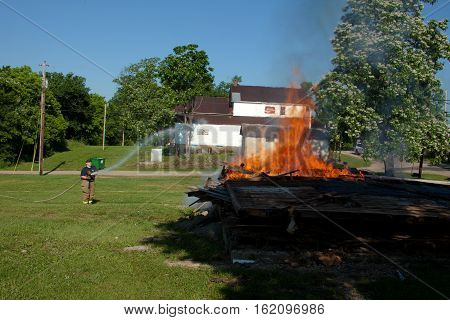 June 7, 2013:  A firefighter put out the flames of a controlled fire of an old building in Lesterville, Missouri.