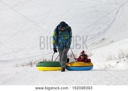 Father And Daughter With Snow Tube In Sun Winter Day