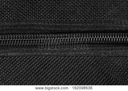 closeup detail of black zipper with canvas texture