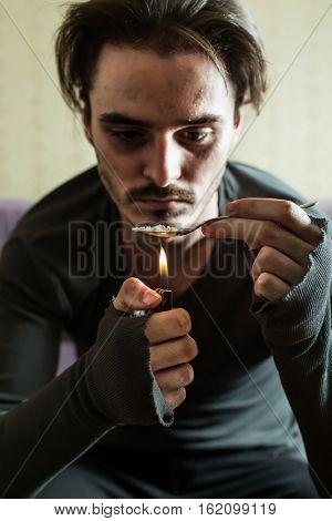 Addict in depression preparing dose of heroin.